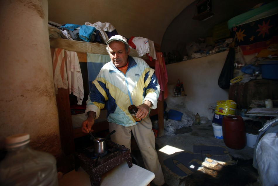 Sostis makes cofee in his 10 sqm house on the volcanic islet of Palaia Kameni located in the caldera of Santorini