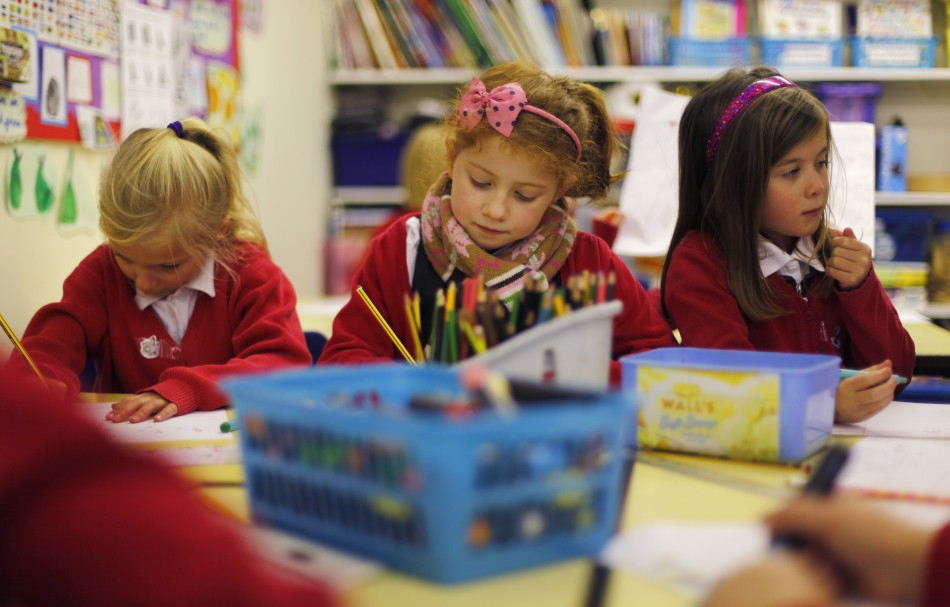 Pupils Freya Sloane, Maddie Malloy, and Isabelle Sloane, concentrate on their drawings at Watlington Primary School in Watlington, southern England