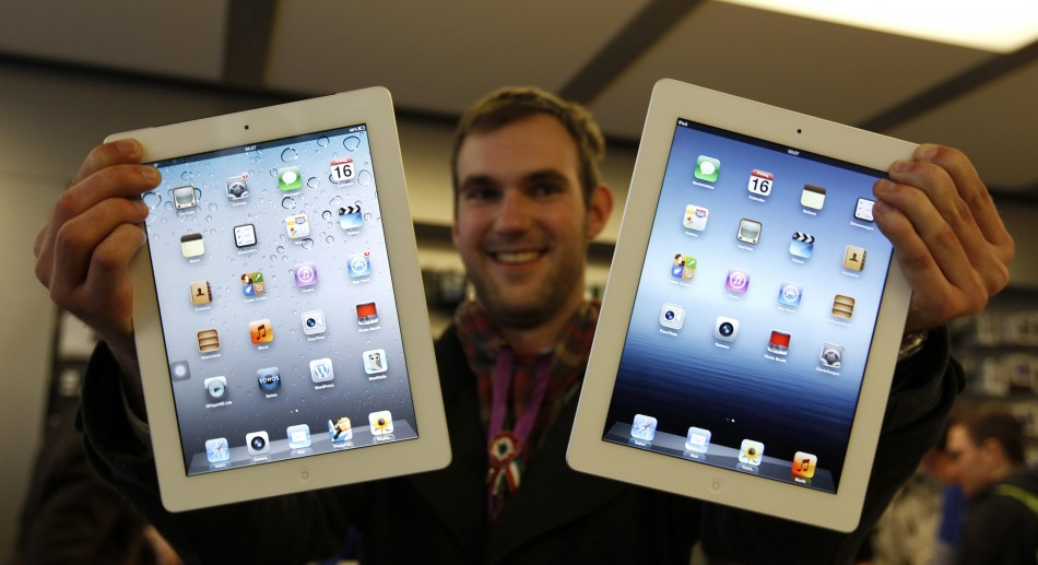 Balazs Gal, one of the first new iPad buyers in Germany, poses with a new iPad and an iPad2 in the Apple store in Munich