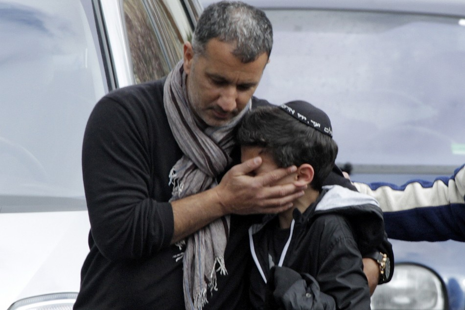 A school student is escorted as he leaves the Ozar Hatora Jewish school in Toulouse, southwestern France