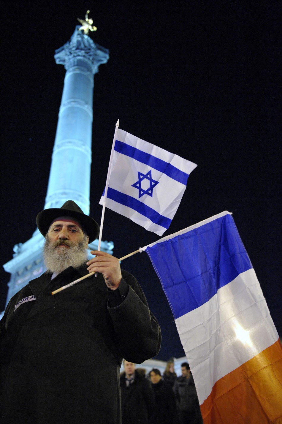 A man holds French and Israeli flags