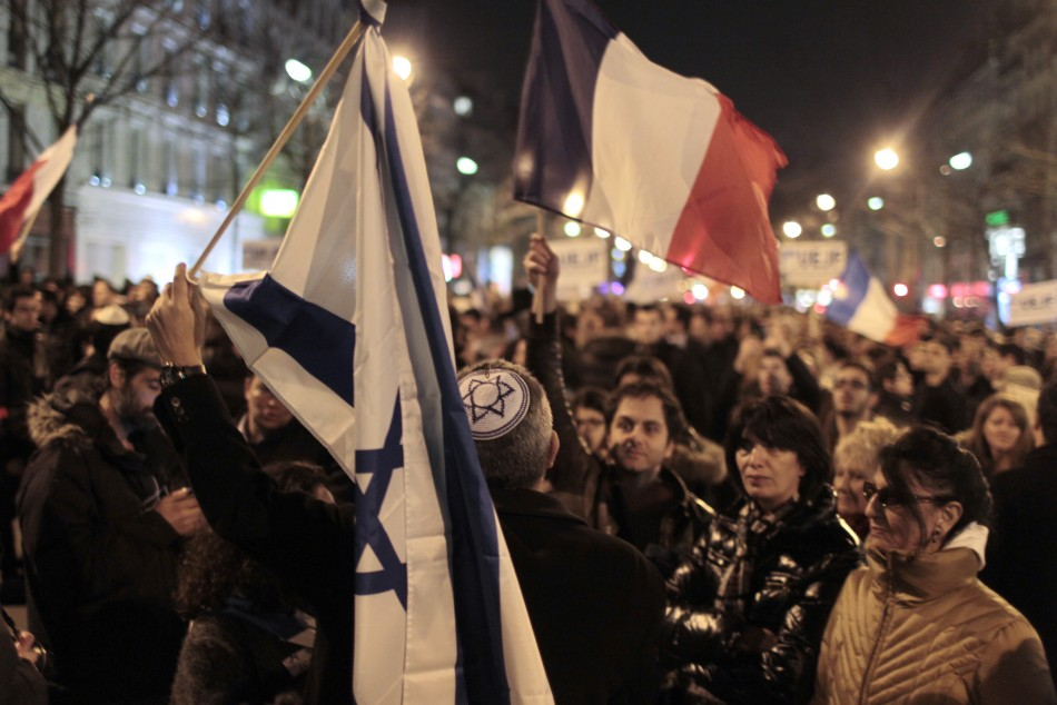 People hold French and Israeli flags