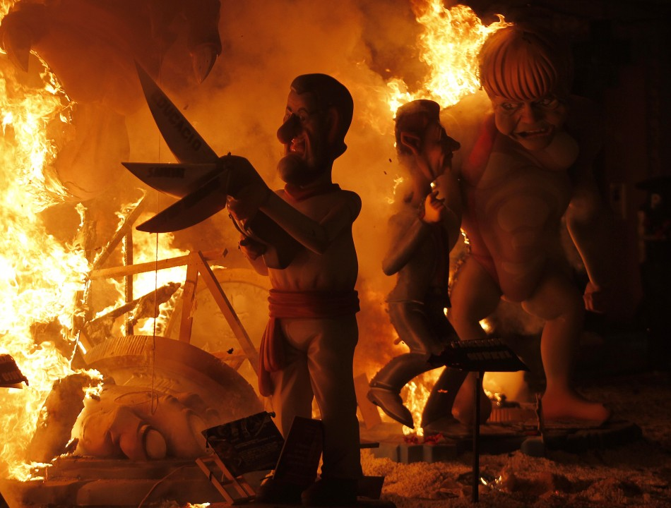 Effigies of Spains Prime Minister Rajoy and German Chancellor Merkel burn during the finale of the Fallas festival in Valencia
