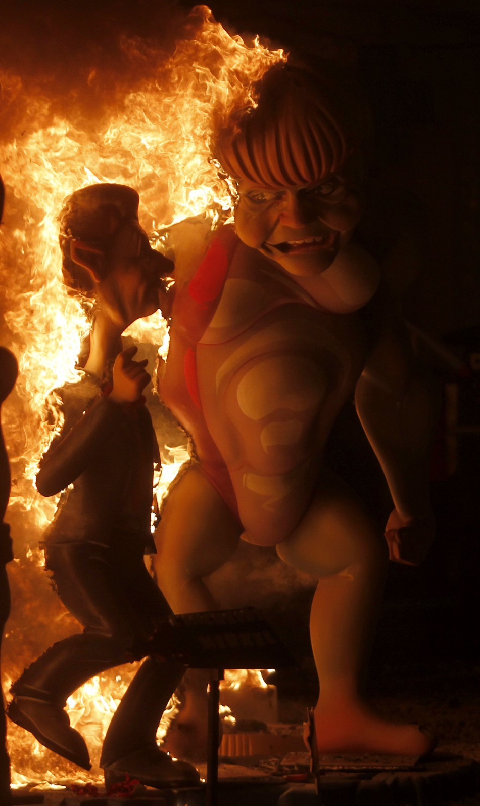 An effigy of German Chancellor Angela Merkel burns during the finale of the Fallas festival in Valencia