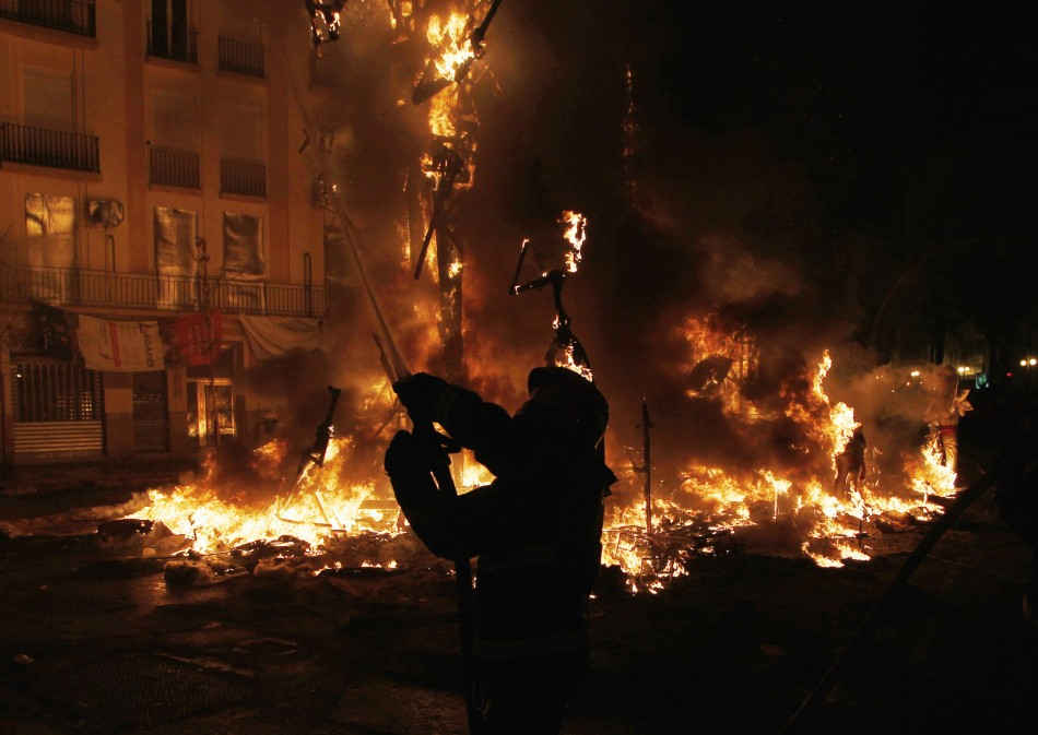 A firefighter sprays water to control the burning of effigies during the finale of Fallas festival in Valencia