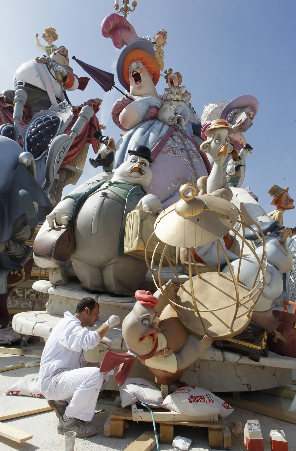 "A craftsman puts the finishing touches on a figure ahead of the ""Fallas"" festival in Valencia"
