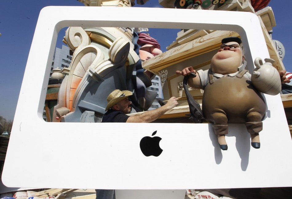 "A craftsman puts finishing touches on a figure sitting on a representation of an Apple computer ahead of the ""Fallas"" festival in Valencia"