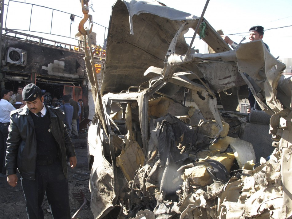 Iraqi security forces inspect the site of a bomb attack in Hilla, Reuters