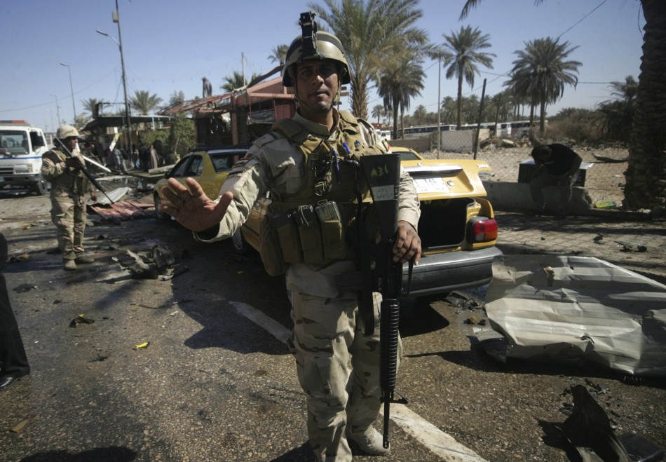 Iraqi security forces stand guard at the site of a bomb attack in Kerbala, Reuters