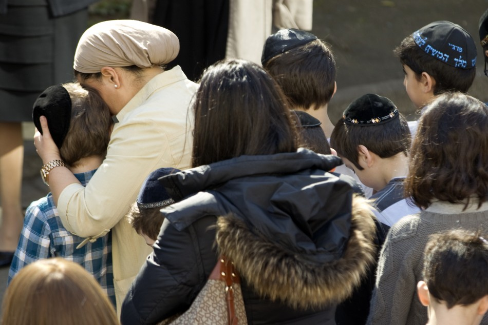 A teacher comforts a school child as they observe a minute of silence at a Jewish school in Paris