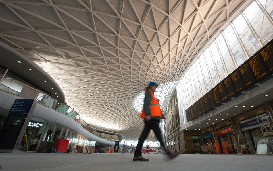 A worker walks in the new Kings Cross rail station redevelopment in London