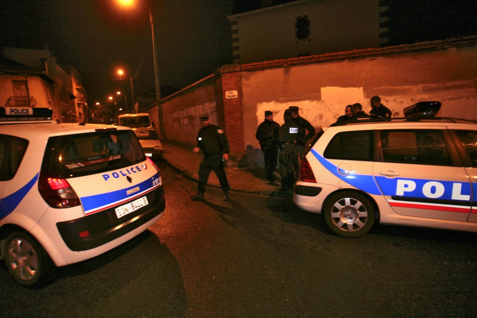Policemen block streets as a raid on a house to arrest suspects in the killings of three children and a rabbi on Monday