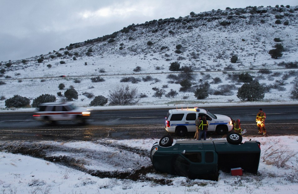 Firefighters and police officers stand near a pick-up truck that rolled on its side after the driver lost control along Interstate-17 in Yavapai County