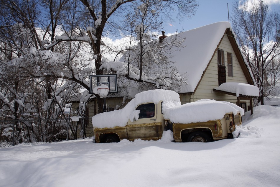 Snow blankets a pick-up truck and a house after a winter storm in Flagstaff