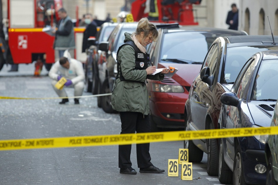 Police conduct thier investigaton near the Indonesian embassy where a package bomb exploded in Paris