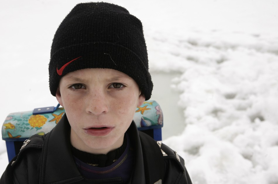 A child crossing the lake of Batllava to go to school poses for a photo in Kosovos village of Orllan