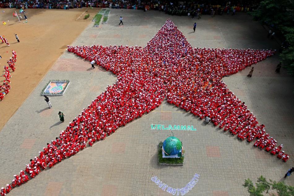 Schoolchildren dressed as Santa Claus form the shape of a star