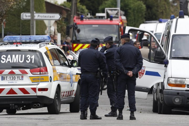 French CRS police block a street during a raid on a house to arrest a suspect in the killings of three children and a rabbi on Monday at a Jewish school, in Toulouse