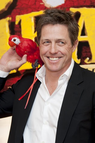 Hugh Grant poses with parrot at premiere of The Pirates in an Adventure with Scientists