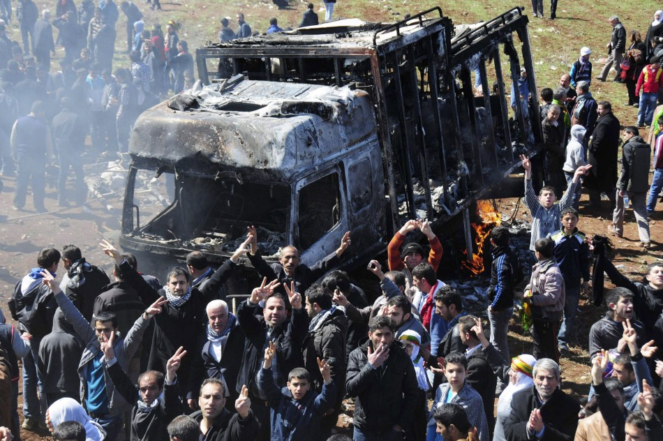 Kurdish demonstrators flash victory signs in front of a burnt-out vehicle in Diyarbakir, southeastern Turkey