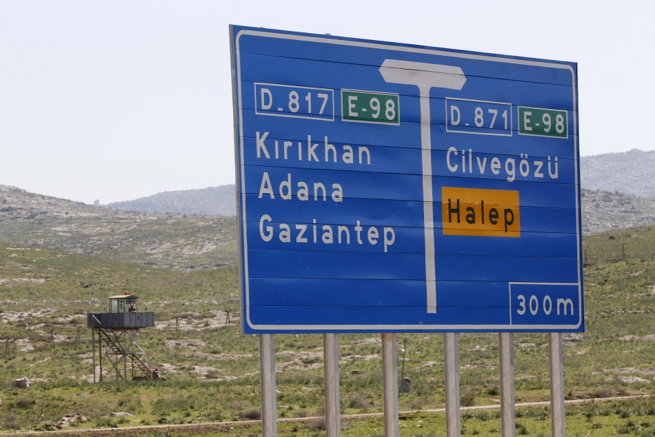 A Turkish soldier stand in a watchtower with a road sign showing directions to Cilvegozu border crossing and Syrian city of Aleppo in the town of Reyhanli in Hatay province on the Turkish-Syrian border