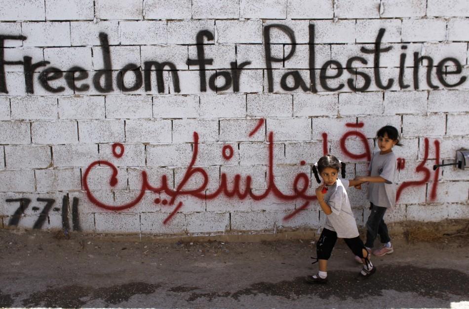 Palestinian girls walk past wall scrawled with graffiti in Dehaishe refugee camp, Bethlehem