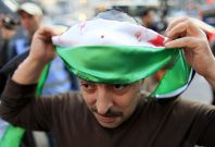 A Syrian protester gets ready to join the anti regime procession in Syria