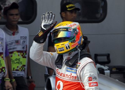 McLaren Formula One driver Hamilton waves after taking the pole position in the qualifying session of the Malaysian F1 Grand Prix at Sepang International Circuit outside Kuala Lumpur