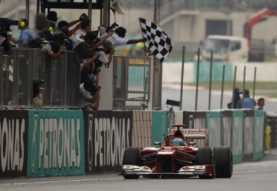Ferrari Formula One driver Alonso takes the checkered flag to win the Malaysian F1 Grand Prix at Sepang International Circuit outside Kuala Lumpur