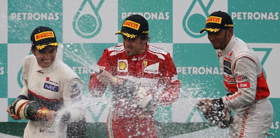 Sauber039s driver Perez, Ferrari039s driver Alonso and McLaren039s driver Hamilton celebrate during the podium ceremony following the Malaysian F1 Grand Prix at Sepang International Circuit