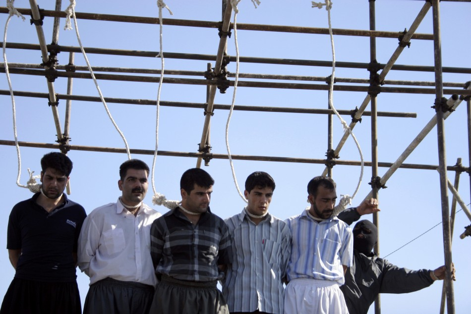 A policeman prepares five men for their hanging in Mashhad