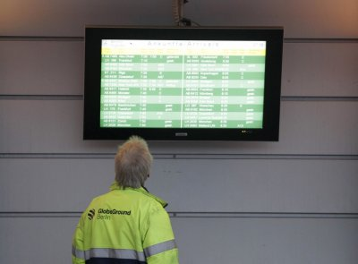 A worker looks at an arrival information board