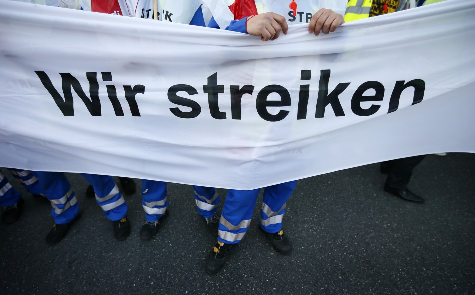 Members of Germanys public sector workers union Verdi hold a banner