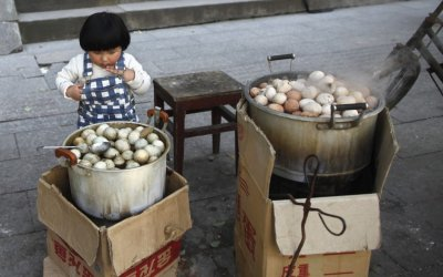 A girl looks at a pot of regular hard-boiled eggs, next to a pot cooked in boys urine in Dongyang