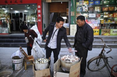 Vendor Ge Yaohua looks at a customer pointing at a pot of hard-boiled eggs cooked in boys urine in Dongyang