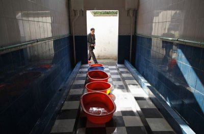 A man walks into a primary school toilet where containers are placed to collect urine passed out by boys, in Dongyang