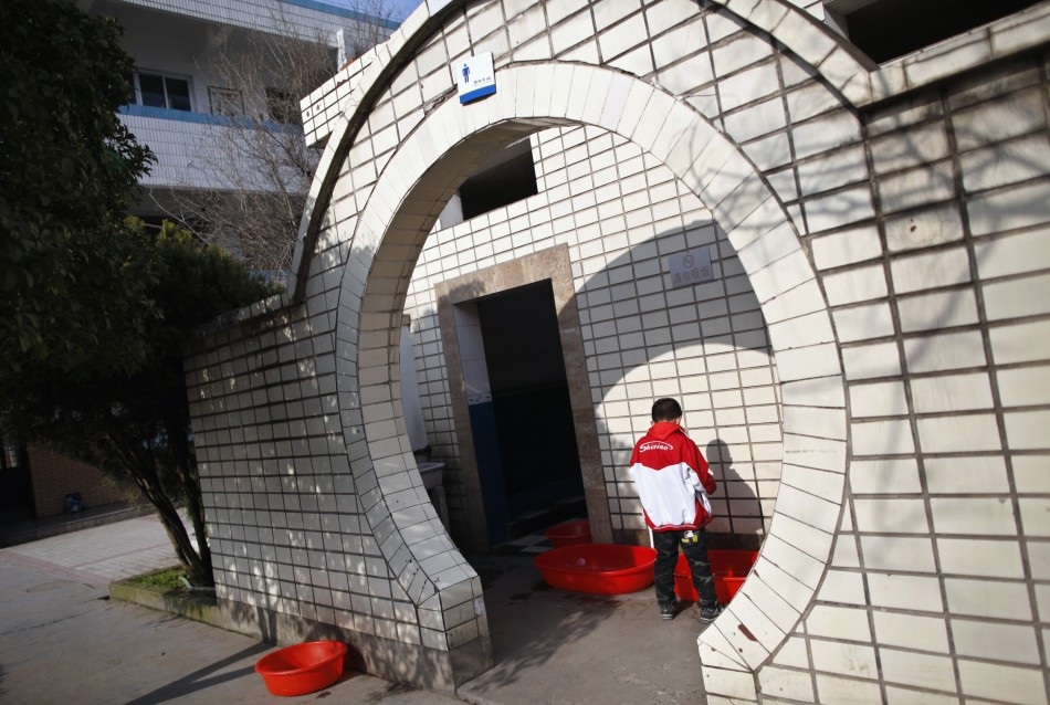 A boy urinates into a container at a primary school in Dongyang