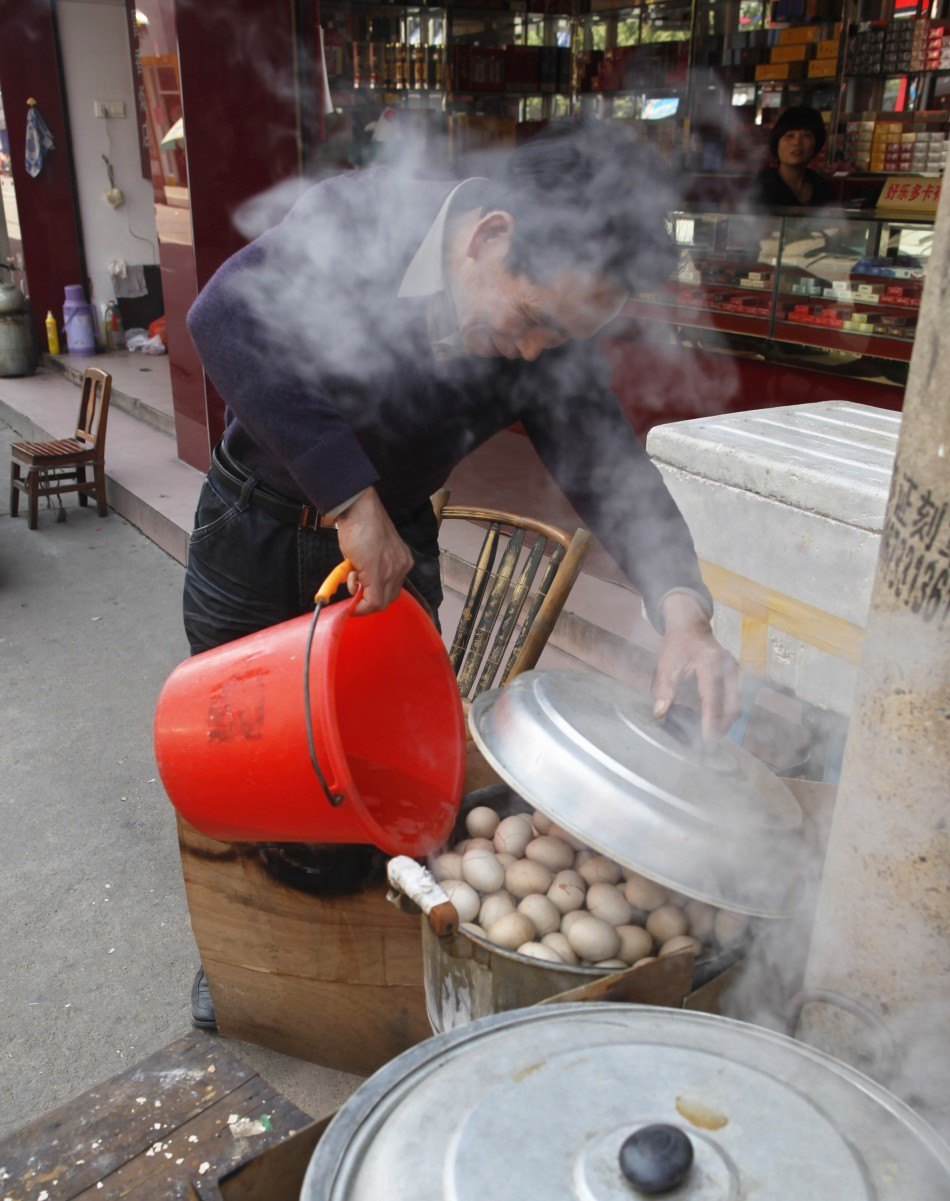 A vendor pours a bucket of boys' urine into a pot of hard-boiled eggs at his stall in Dongyang