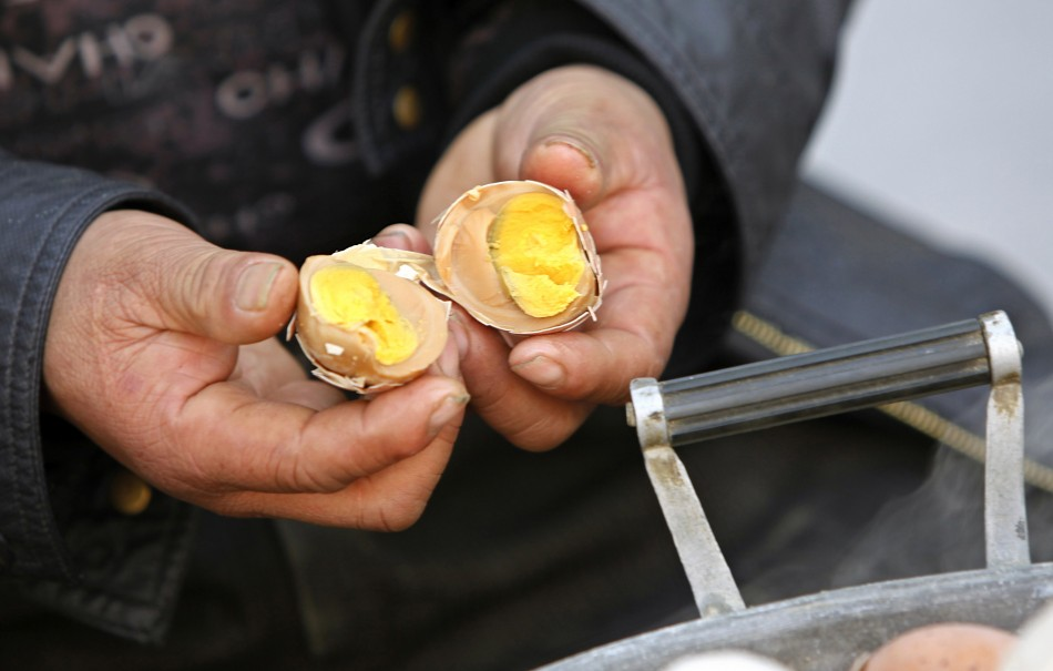 Vendor Ge Yaohua shows the inside of a hard-boiled egg cooked in boys urine at his stall in Dongyang
