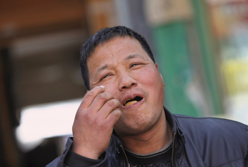 Vendor Ge Yaohua eats a hard-boiled egg cooked in boys urine at his stall in Dongyang