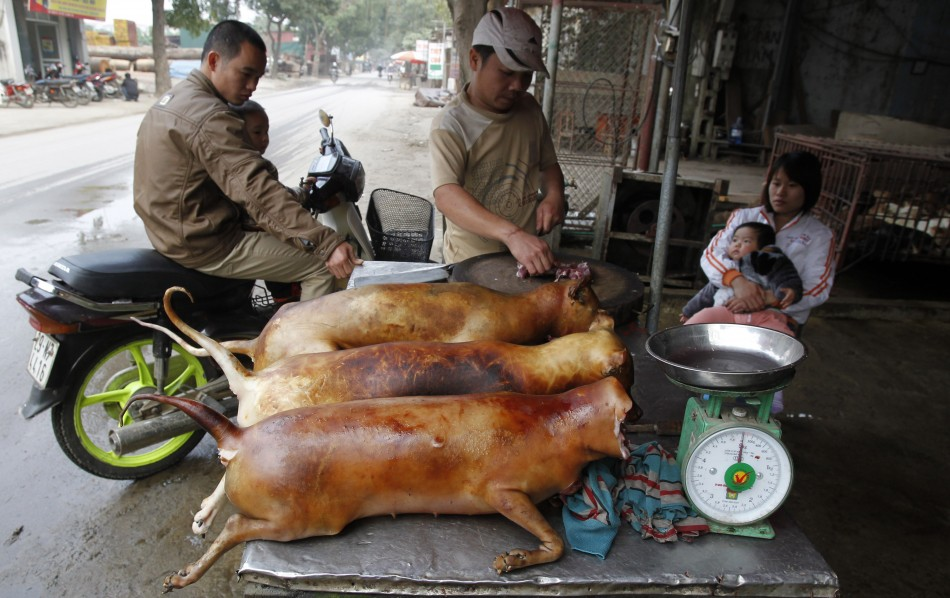 A vendor cuts slaughtered dogs for sale at his roadside stall in Duong Noi village, outside Hanoi