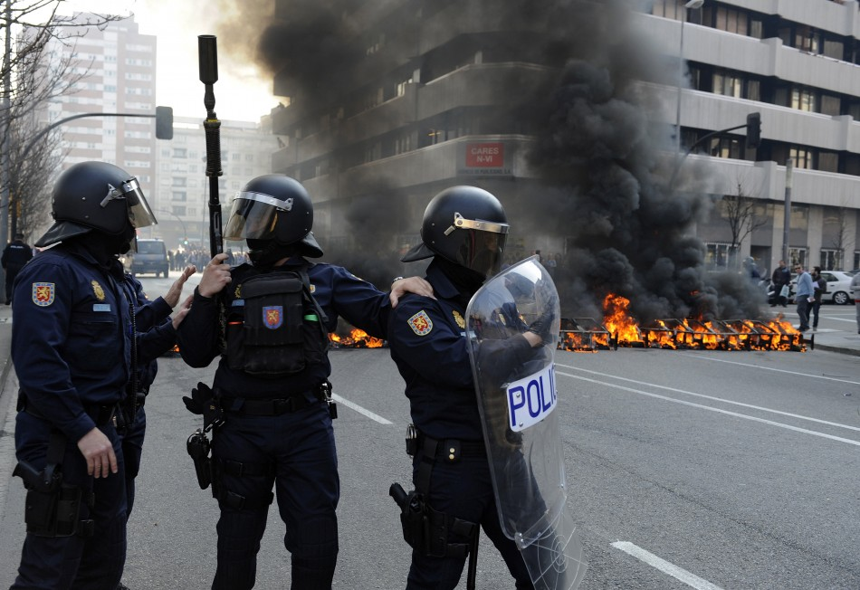 Riot Police stand in front of a burning barricade during Spain's general strike in Gijon