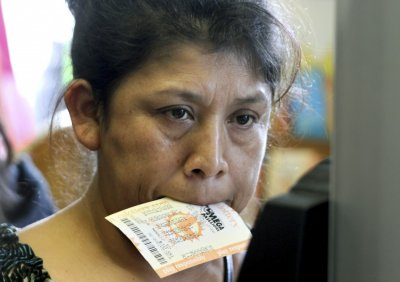 A woman holds a Mega Millions lottery ticket in her mouth in Lawndale
