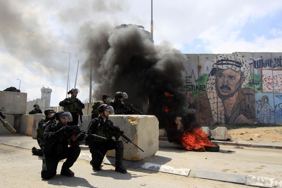 Israeli soldiers take position during clashes with Palestinian protesters at a demonstration marking Land Day at Qalandiya checkpoint