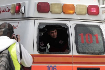 A medic looks through a broken ambulance car window during clashes at a demonstration marking Land Day at Qalandiya checkpoint