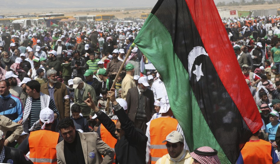 A man holds up a Libyan flag during joint activities near the Jordanian side of the Jordan River to mark Land Day