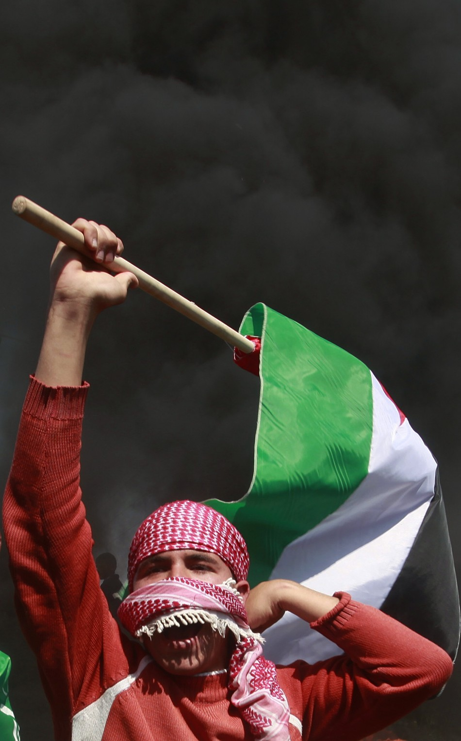 A Palestinian protester holds a flag during a protest marking Land Day, near the border between Israel and the northern Gaza Strip