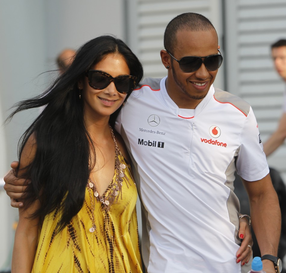 McLaren Formula One driver Hamilton walks with his girlfriend Nicole after the qualifying session of the Malaysian F1 Grand Prix at Sepang International Circuit outside Kuala Lumpur