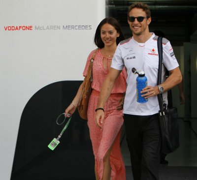 McLarens driver Button and his girlfriend, Jessica Michibata, walk in the paddock area after the qualifying session of the Malaysian F1 Grand Prix at Sepang International Circuit