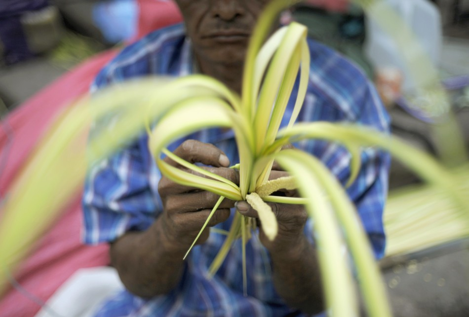 A man works a palm branch for sale outside a church in Tegucigalpa